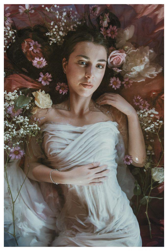 modella posa in una vasca piena di fiori | fotografia come un quadro